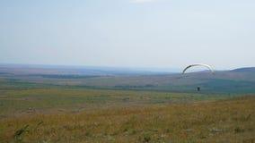Le vol extrême de parapentiste contre un ciel bleu clair, rayon de soleil brille dans la caméra L'expérience de vol de Paraglide  banque de vidéos