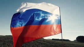 Le vol tricolore russe de drapeau dans le mouvement lent et le dos s'est allumé par le soleil dans le paysage banque de vidéos