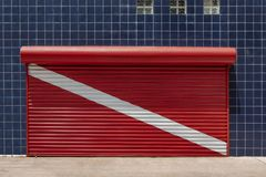 Le volet fermé de magasin a peint au drapeau rouge de plongée à l'air avec un wal photographie stock