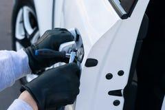 Le voleur a cassé la serrure sur la porte de la voiture blanche et l'a ouverte, plan rapproché images stock