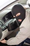 Le voleur dans le masque vole la voiture Image libre de droits