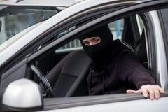 Le voleur de voiture entre dans une voiture volée image libre de droits