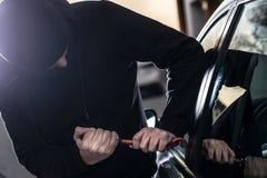 Le voleur de voiture essaye de pénétrer par effraction dans la voiture avec le pied-de-biche image libre de droits