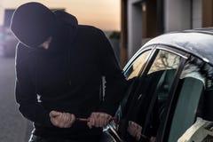 Le voleur de voiture essaye de pénétrer par effraction dans la voiture avec le pied-de-biche Images stock