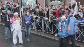 Le volontaire donnent la foule cinq Flamme olympique de Sotchi de course de relais dans le St Petersbourg Porteur de flambeau Aly banque de vidéos