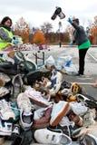 Le volontaire jette des espadrilles en l'air dans la pile de chaussure à réutiliser l'événement Photo libre de droits