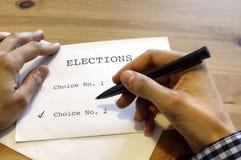 Le vote sur la table avec des mains Photos stock