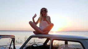 Le voyage d'été à la voiture, musique de écoute de fille sur des écouteurs sur la voiture de toit, femelle apprécient la bonne mu clips vidéos