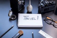 Le voyage est écrit sur le petit bloc-notes avec des crayons Photo stock