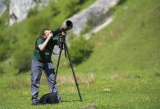 Le voyage professionnel sur le videographer d'emplacement et de nature/photographe équipent photographier la faune image libre de droits