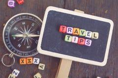 Le VOYAGE TIP le bloc de mot sur le signage et la boussole en bois couleur fanée d'effet Photographie stock