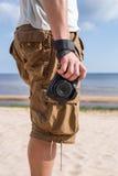 Le voyageur admire la vue de la mer, tenant l'appareil-photo au prêt Image libre de droits