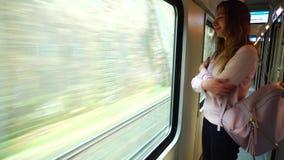 Le voyageur assez féminin quitte la ville et se tient dans le train près de la grande fenêtre de transport banque de vidéos