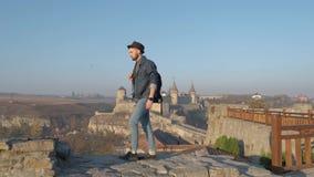 Le voyageur d'homme avec le sac à dos explore la ville regardant la vue panoramique de la ville et de la côte le concept de banque de vidéos