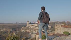 Le voyageur d'homme avec le sac à dos explore la ville regardant la vue panoramique de la ville et de la côte le concept de clips vidéos
