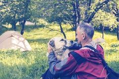 Le voyageur d'homme joue avec le grand chien dans un camp Images libres de droits