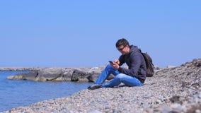 Le voyageur d'homme s'assied sur la plage de pierre de mer, les sourires et les types message sur le smartphone banque de vidéos