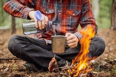 Le voyageur d'homme verse l'eau d'une bouteille dans une tasse en métal Photo stock