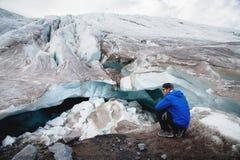 Le voyageur dans un chapeau et des lunettes de soleil s'assied dans les montagnes neigeuses sur le glacier Voyageur dans un envir photos stock