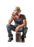 Le voyageur de jeune homme prend un tir tout en se reposant sur la valise au-dessus de W Images stock