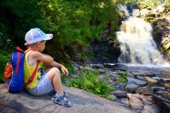 Le voyageur de petit garçon avec le sac à dos s'assied près des chutes Images stock