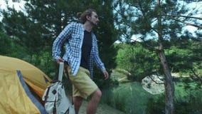 Le voyageur de randonneur de jeunes hommes va le long de l'étang Sur le sac à dos de marche arrière Un homme marche hors d'une te clips vidéos