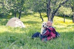 Le voyageur de sourire d'homme étreint avec le grand chien dans un camp Photos libres de droits