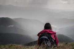 Le voyageur en voyage de trekking aux montagnes se repose au secteur de montagne et regarde la pluie lourde de tonnerre se renver Photographie stock