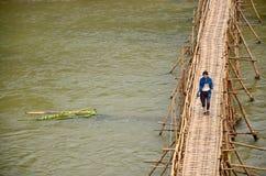 Le voyageur et les personnes laotiennes utilisent le pont en bambou pour la promenade sur la croix Images stock