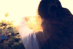 Le voyageur féminin font la main en forme de coeur avec le soleil Photos stock