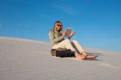 Le voyageur heureux, jeune femme seul s'assied dans la plage Photographie stock libre de droits