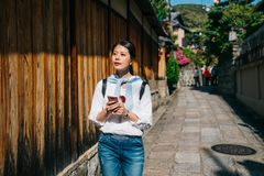 Le voyageur lit le guide par son téléphone portable photographie stock