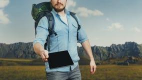 Le voyageur méconnaissable d'homme avec le sac à dos tient un comprimé numérique photos stock
