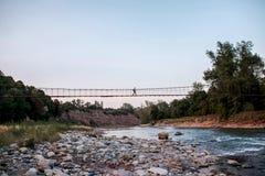 Le voyageur marche le pont au-dessus de la rivière image stock