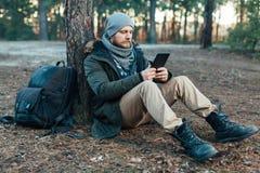 Le voyageur masculin beau adulte s'assied sur la forêt de pin d'automne près de l'arbre, se tenant au concept de repos de destina photos stock