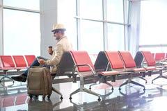 Le voyageur masculin mûr joyeux utilise le smartphone dans le terminal Photo stock