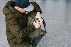 Le voyageur sort une bouteille de l'eau de son sac à dos à la boisson photographie stock libre de droits