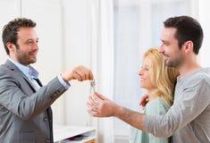 Le vrai agent immobilier fournit des clés de nouvelle maison à de jeunes couples Image stock