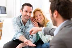 Le vrai agent immobilier fournit des clés de nouvelle maison à de jeunes couples Images libres de droits