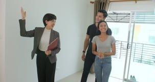 Le vrai agent immobilier professionnel montre la maison moderne à un jeune couple banque de vidéos