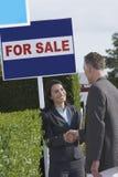 Le vrai agent immobilier serrant la main à l'homme à coté en vente signe Image stock