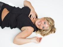 Le vrai milieu a vieilli la femme s'étendant sur le plancher blanc Photographie stock libre de droits