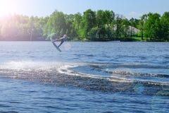 Le wakeboarder d'athlète exécute un saut avec un saut périlleux dans le ciel photos stock