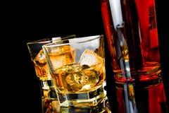 Le whiskey deux avec de la glace en verres s'approchent de la bouteille sur le fond noir Images libres de droits