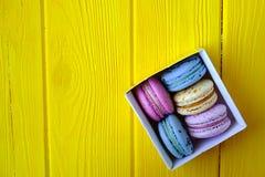 Le whith multi français de buiscits de macarons de goûts fleurit sur le fond en bois Images libres de droits