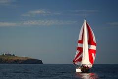 Le yacht avec une voile rouge près d'île. Image stock