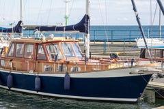Le yacht bleu de vintage en bois se tient près du pilier photographie stock libre de droits