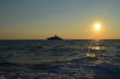 Le yacht de moteur flotte dans le coucher du soleil Image libre de droits