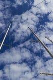 Le yacht mâte haut dans le ciel bleu avec de grands cumulus blancs photo stock