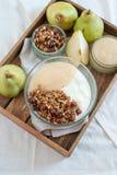 Le yaourt avec les poires cuites et la maison ont fait la granola images stock